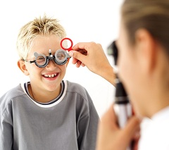 Young Medical Professional Checking the Eyes of Young Boy (8-10) --- Image by © Royalty-Free/Corbis